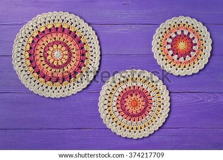 three crochet pattern coasters on purple wooden  background - stock photo