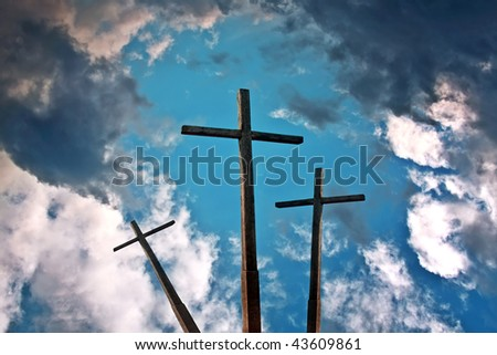 Three crosses above blue sky with clouds - stock photo