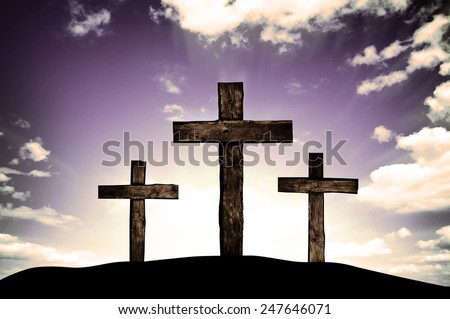 Three crosses on a hill and dark sky with sun rays
