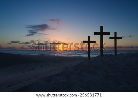 Three crosses on a sand dune next to the ocean with a cloudy sunrise - stock photo