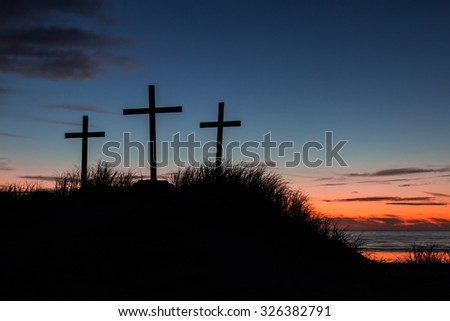 Three Crosses on a sand dune with the sun set behind them.