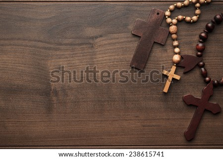 three crosses on the brown wooden table background - stock photo