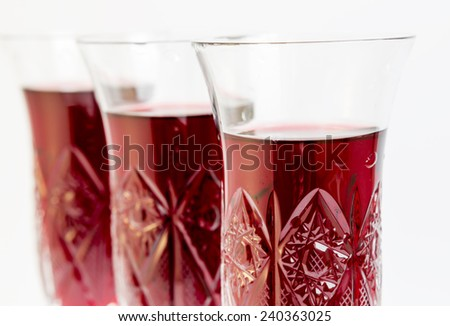 Three crystal glasses of red wine isolated on white.