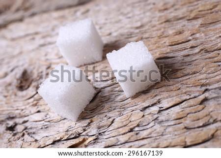 Three cubes of sugar. Refined sugar on the table. Cubes of sugar on the table. Sweet foods and sweets. Sugar on the wooden table. Subject macro shooting. Macro sugar. - stock photo