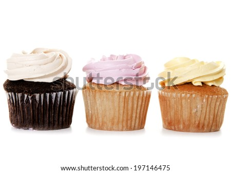 Three cupcakes topped with mounds of swirled icing. - stock photo
