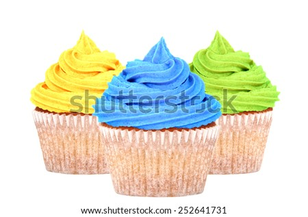 Three cupcakes with colorful yellow, blue and green frosting isolated on a white background - stock photo