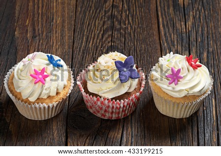 Three cupcakes with cream on wooden table close up - stock photo