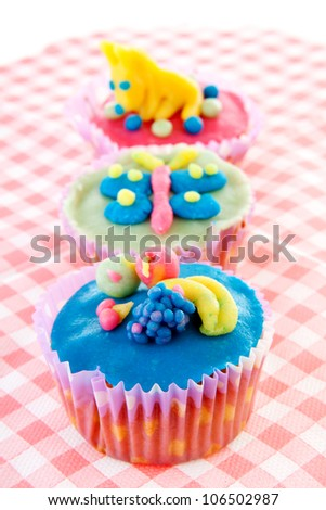 three cupcakes with marzipan decoration on napkin