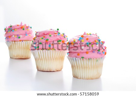 Three cupcakes with sprinkles in a line isolated on white - stock photo