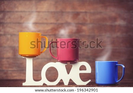 Three cups of coffee and word love on wooden table. - stock photo