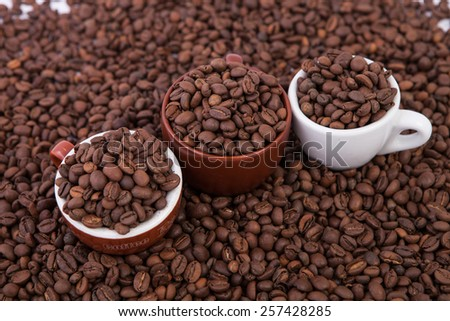 three cups of coffee full of coffee beans. Close-up.