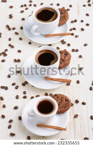 Three cups of coffee on the white table with coffee beans