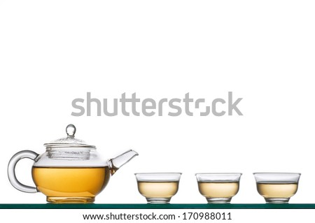 Three cups of tea and a teapot - stock photo