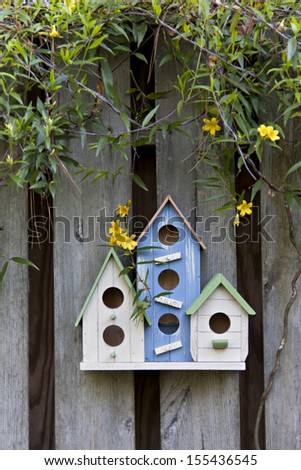 Three cute birdhouses with spring flowers and old rustic wooden fence - stock photo