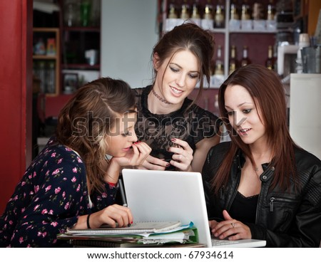 Three cute female students studying with a book and laptop in a cafe