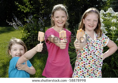 Three cute girls eat popsicle in the garden. - stock photo