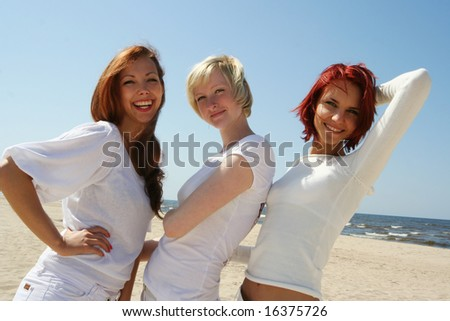 three cute girls relaxing on the beach - stock photo