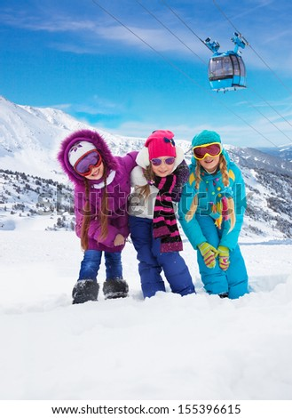 Three cute girls snowboarders in the mountain with ski lift on background - stock photo