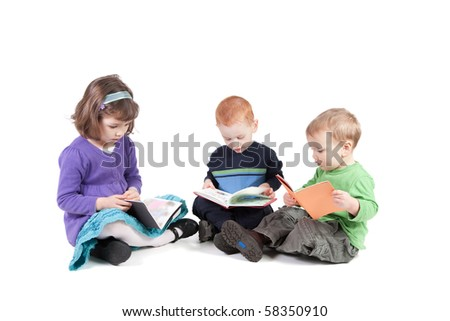 Three cute kids reading books while sitting on floor.  Isolated on white with shadows.