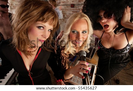 Three cute ladies singing at a 1970s Disco Music Party - stock photo