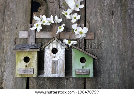 Three cute little birdhouses on rustic wooden fence with Dogwood flowers  on them - stock photo