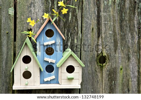 Three cute little birdhouses on rustic wooden fence with yellow flowers on them - stock photo
