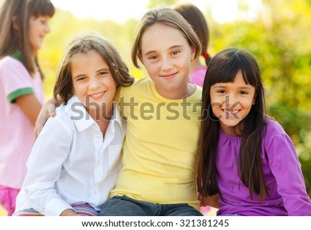 Three cute little girls smiling in nature. Elementary age. Other kids in the background.