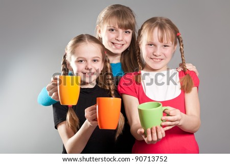 Three cute little girls with colorful mugs