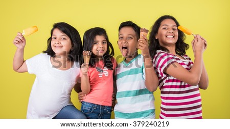 three cute little indian kids eating ice cream, asian girls and boy and ice cream, isolated on green background - stock photo