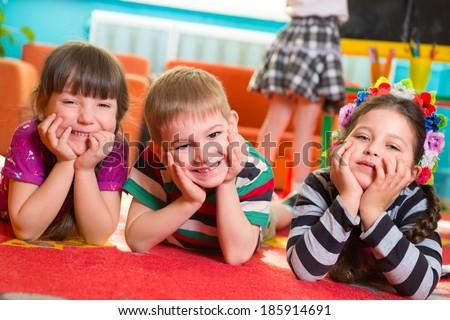 Three cute preschoolers lying on floor with hands under cheeks - stock photo