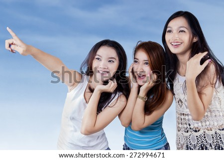 Three cute teenage girls pointing and looking at copyspace under blue sky - stock photo