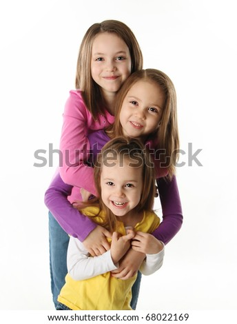 Three cute young sisters hugging each other, isolated on white - stock photo