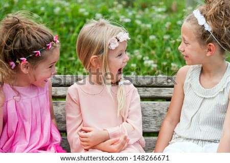 Three cute youngsters on wooden bench having fun. - stock photo