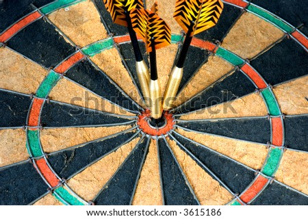 three darts hitting target on dart board