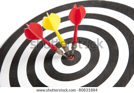 Three Darts hitting the middle of dartboard - stock photo