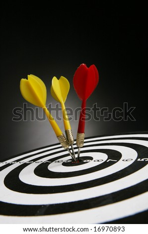 Three darts on bull's eye of a dart board - stock photo
