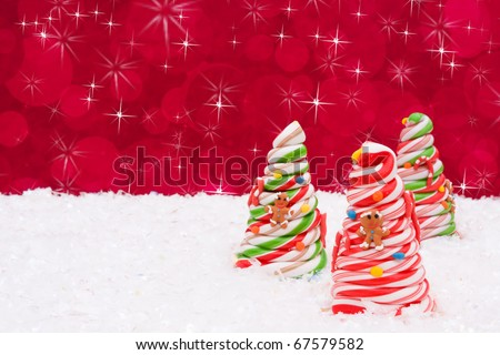 Three decorated candy cane trees on snow with a red background, Christmas Time - stock photo