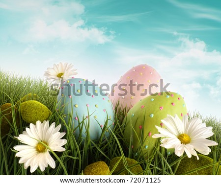 Three decorated easter eggs in the grass with daisies - stock photo
