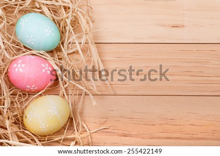 Three decorated Easter eggs on a wood background for copy space - stock photo