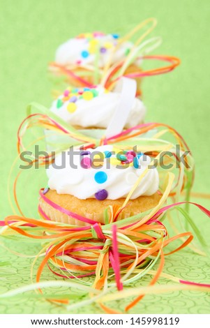 Three decorated vanilla cupcakes on a green background - stock photo