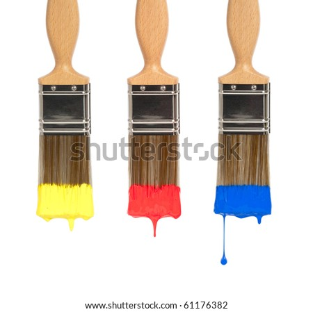 Three decorators paint brushes dripping with different coloured paints, yellow, red and blue - stock photo