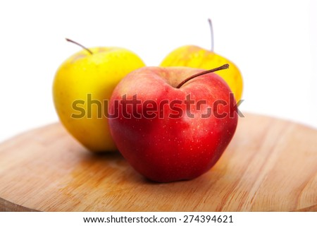 Three delicious apples on a cutting board. One red apple and two yellow. Apple - stock photo