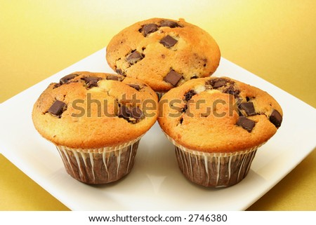 three delicious choc chip muffins on a square plate with a golden background - stock photo