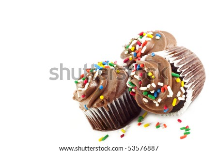 Three delicious chocolate cupcakes with chocolate frosting and colored sprinkles - stock photo