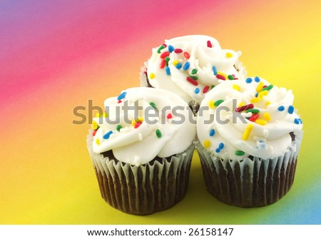 Three delicious chocolate cupcakes with vanilla frosting and sprinkles on a bright rainbow colored background with copy space - stock photo