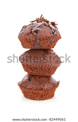 Three delicious chocolate muffins arranged on each other isolated on white background.