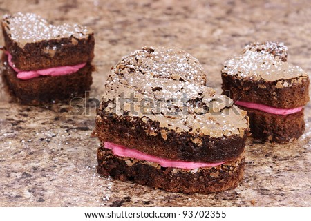 Three delicious homemade heart shaped brownies piped with strawberry or raspberry flavored frosting.  Shallow depth of field. - stock photo