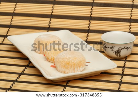 Three delicious japanese mochi rice cakes on white plate standing on striped bamboo mat background with white porcelain cup. Shallow dof. Focus on first cake. - stock photo