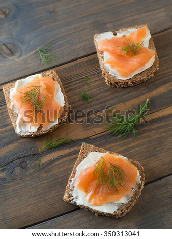 Three delicious sandwiches from the top with salmon on a wooden background - stock photo