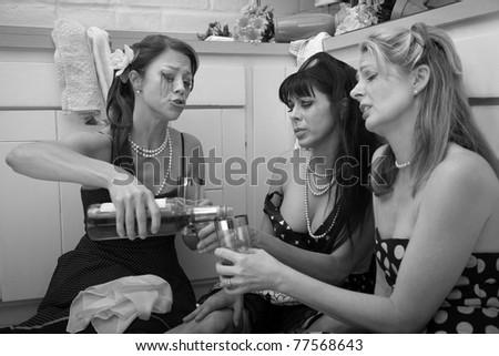 Three depressed woman drinking alcohol - stock photo